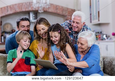 Multi-generation family waving hands while using digital tablet for video chat at home