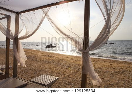 Beautiful view of a beach in sunset through the curtains of a beach bed