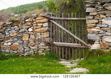 Rustic handmade wooden gate made from natural wooden poles in a stone wall with a path leading to a rural hillside.