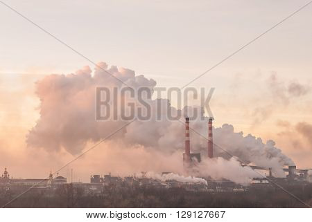Industrial landscape with pipes and smoke from big plant