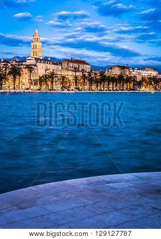 Split is touristic and mediterranean town on Adriatic sea, a view in blue hour coastline cityscape.