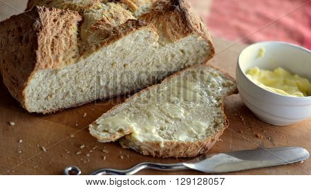 Soda Bread Loaf with buttered slice and small pot of butter.