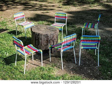 Colorful chairs and wooden table on the lawn. Garden party. Light and shadow.