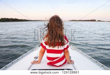 Cute little girl enjoying ride on yacht at sunset
