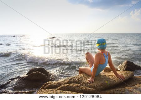 Happy little girl in a bathing suit swim cap goggles at the beach