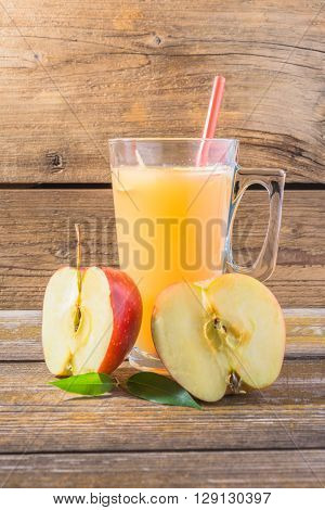 Fresh apple juice in glass on wooden background