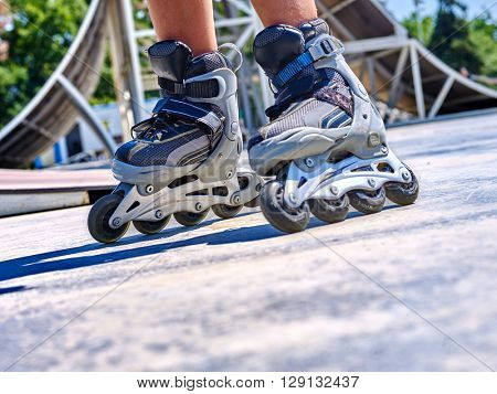 Roller skate close up  in skatepark. low section. Children's feet are shod with roller skates.