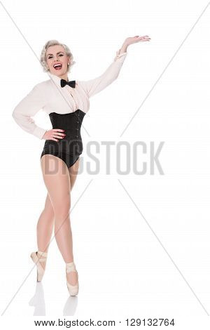 Cute Happy Young Dancer In Corset &  Bow Tie,  Gestures Towards Space For Text, Isolated On White