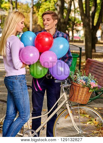 Young couple holding balloons riding on retro bike in the park. Romantic first date.