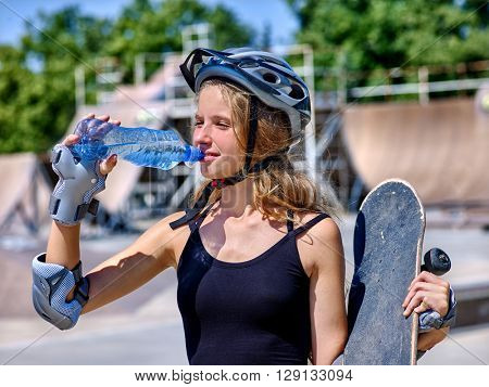 Teen skateboarding his skateboard outdoor. Girl drink water and keeps skateboard.