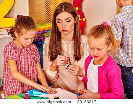 Group kids do origami in kindergarten . Teacher help children.