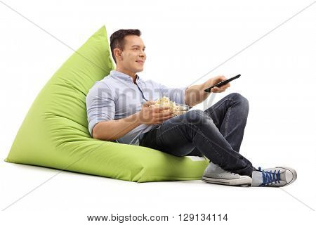 Joyful guy watching TV seated on a green beanbag and eating popcorn isolated on white background