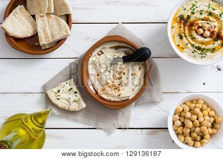 Hummus in bowl and pita bread on white wood table