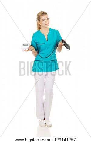 Young similing nurse or doctor with pressure gauge