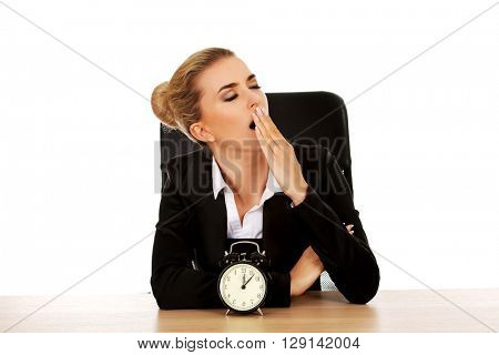 Yawning businesswoman behind the desk