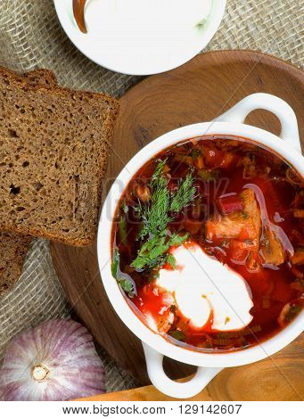 Traditional Soup Borscht with Beet Vegetables and Meat. Top View of Borscht in Bowl closeup on Wooden Plate with Brown Bread Garlic and Sour Cream