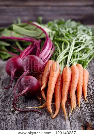 Carrot with beet on a wooden background
