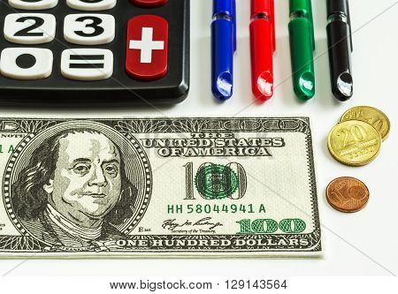 calculator; coins currency notes; pens close-up on a white background money currency business