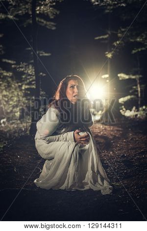 Young scared woman in the forest at night in white dress. Horror scene.