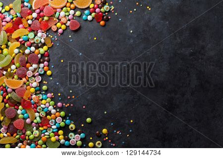 Colorful candies, jelly and marmalade frame over stone background. Top view with copy space