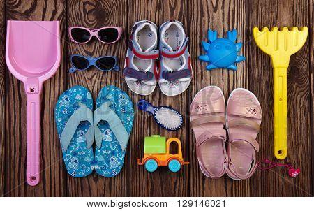 Summer accessories of kids on wooden background