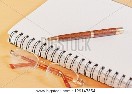Pen notebook and glasses on office desk. Selective focus