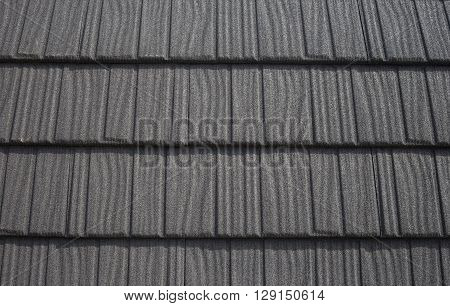 Roof with black bitumen shingles pattern abstract