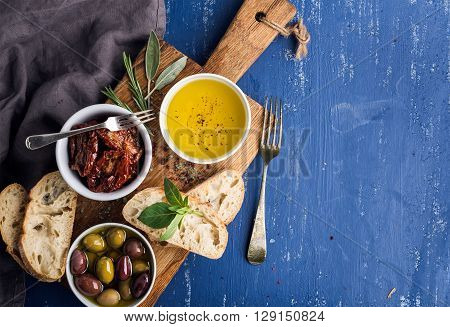 Mediterranean snacks set. Olives, oil, herbs and sliced ciabatta bread on yellow rustic oak board over painted dark blue background, top view, copy space