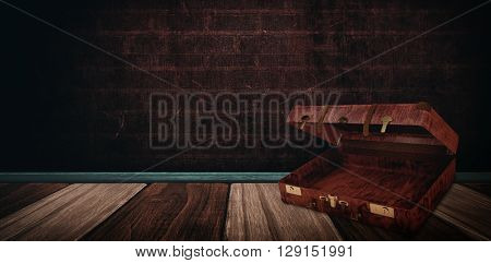 Composite image of opened suitcase against wooden background