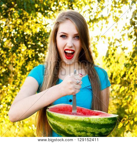 Beautiful blonde girl in a blue dress with long hair holds a half of watermelon with knife