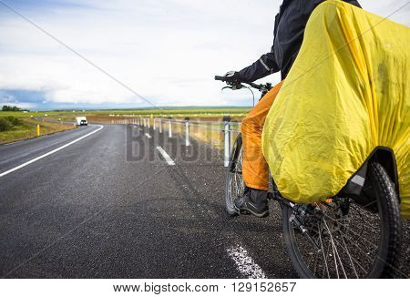 Biker rides on road at sunny summer day in Iceland.