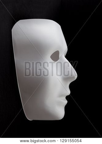White mask without expression emerging from black background