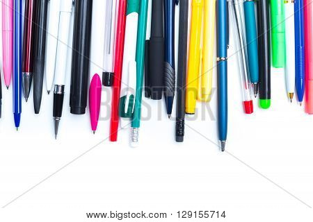 Pens and pencils on white background. top view.
