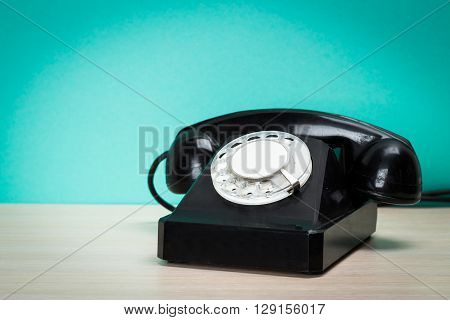old black retro telephone on wooden table.