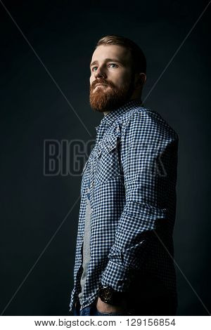 Pensive red bearded handsome stylish man in blue checkered shirt, studio portrait on dark background