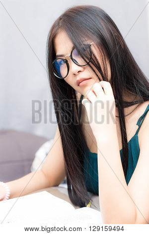 Nerd Asian Girl Sitting On Bed While Reading Book In A Living Room