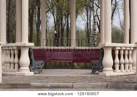 Column gazebo with empty benches in the park. Spring morning