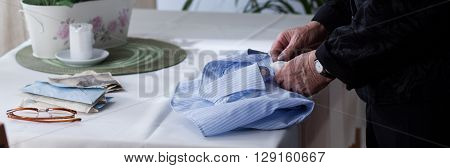Elderly Woman Folding Men's Shirt