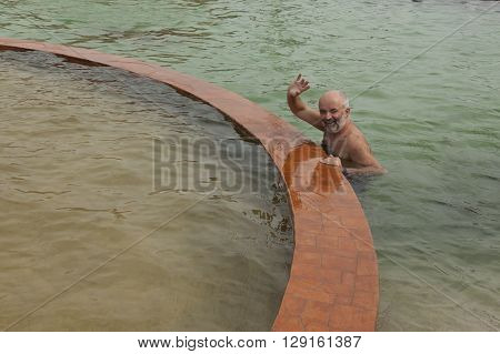 Man in the pool with thermal water of high salinity