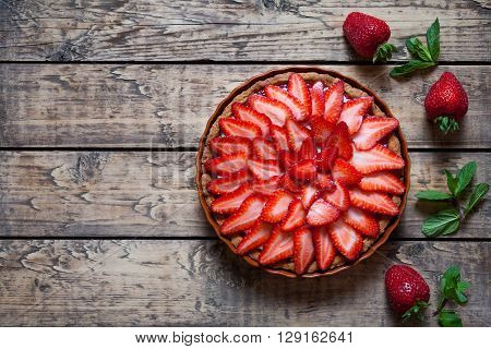 Strawberry tart with cream and mint traditional summer sweet pastry fruit dessert on vintage wooden table background
