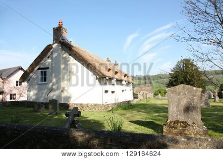 An ancient cottage in a rural Devon Village beside a churchyard with lightly dappled evening sunlight