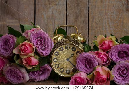 bouquet of pink and violet  fresh roses with golden vintage clock on wood