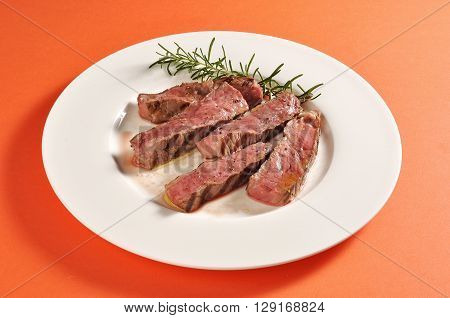 Plate with grilled sliced steak portion and rosemary