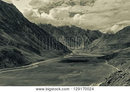 Aerial view of moody and rocky landscape of Kargil with mountain peaks and cloudy sky in background green valley Leh Ladakh Jammu and Kashmir India