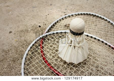 Shuttlecock and badminton racket on cement background.