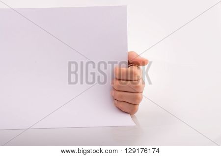 Hand holding a white sheet of paper on a white background