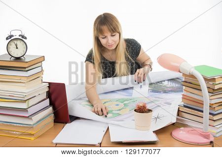 Girl Student Studying Design Drawing Master Plan At A Table Cluttered With Books