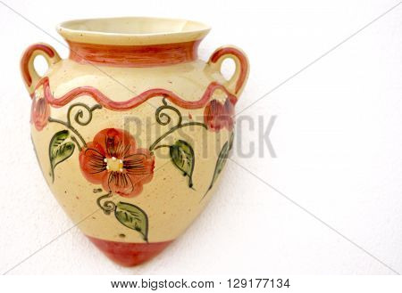 Colors of Spain ceramic mediterranean souvenirs single painted decorative wall pot. Shot in shallow depth of field in the colors of orange olive green and cream on a white wall with room for text and copy space ideal for a poster menu or a holiday event
