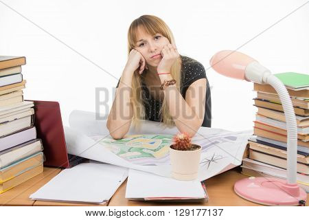 The Girl Is Sad Student Sitting At A Table Crammed With Books, Drawings
