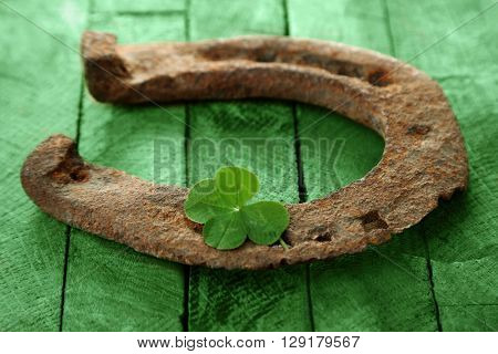 St. Patricks day, old horse shoe with clover leaf on green wooden background